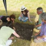 Everyone dives in to carefully trowel back the soil