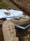 A pehistoric stone carved head alongside the valiant attempt at recreation in wood.