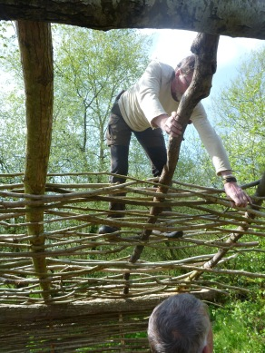 Rob packs down the rods to make a tight weave, whilst bob hands up new sticks.